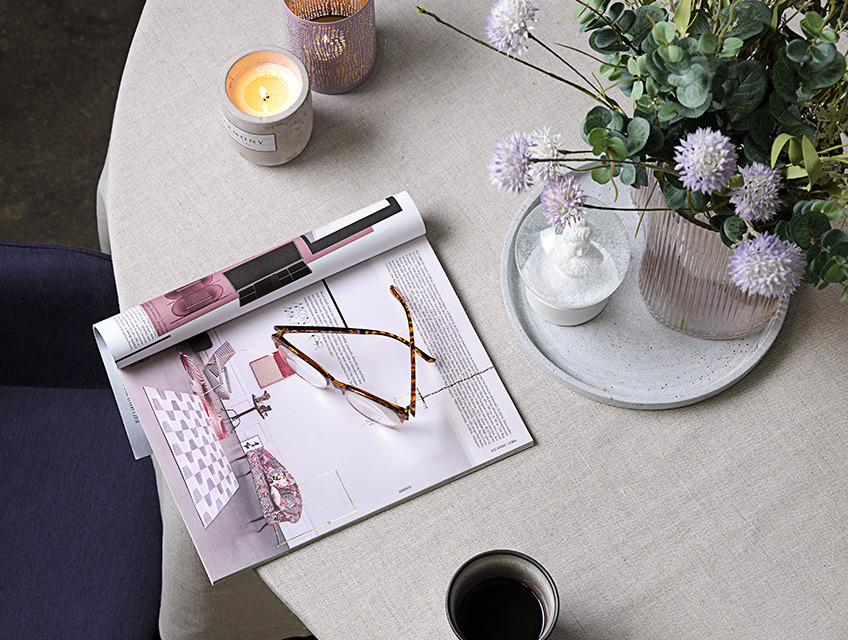 Table with vase and candles, magazine and glasses