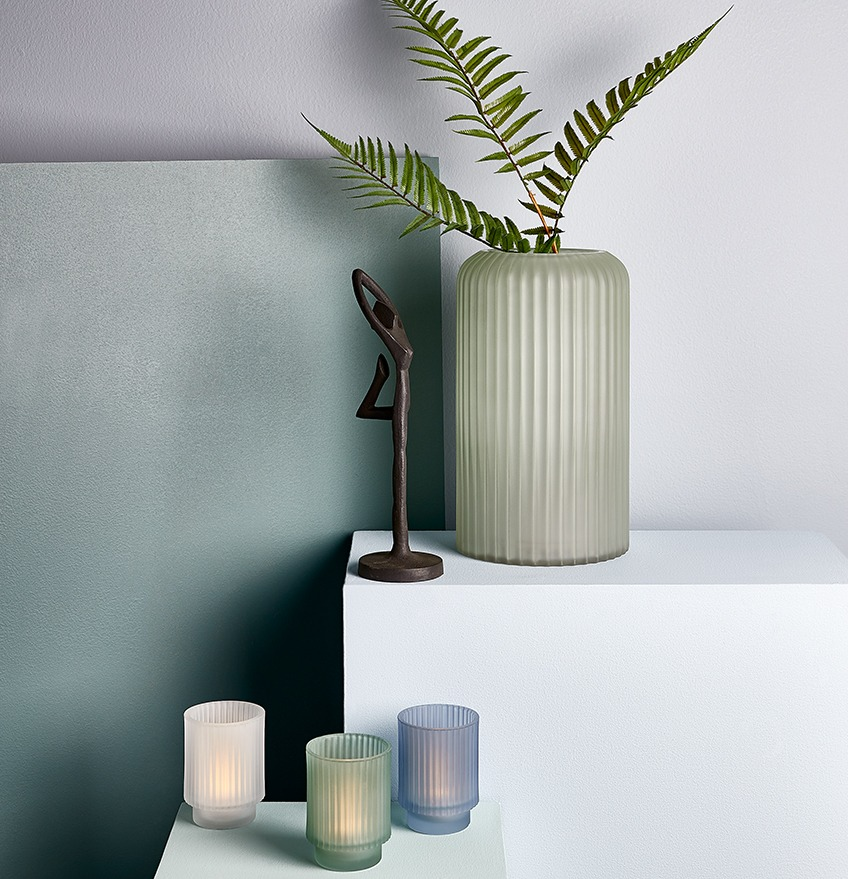 Black ornament, tealight holders and vase with artificial plant, in dusty blue and green colours