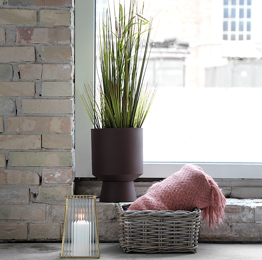 Plant pot with artificial plant, lantern, and basket with a pink throw in front of a window
