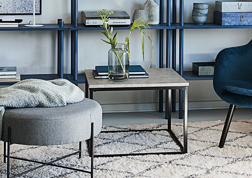 Living room with end table and pouffe in front of a bookcase