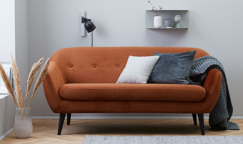 Living room with an orange sofa filled with cushions and a throw