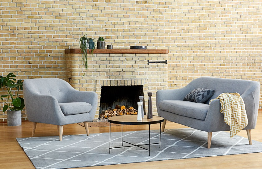 A living room with a grey sofa, a grey armchair and a coffee table
