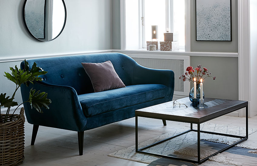 A living room with a blue velvet sofa and a coffee table