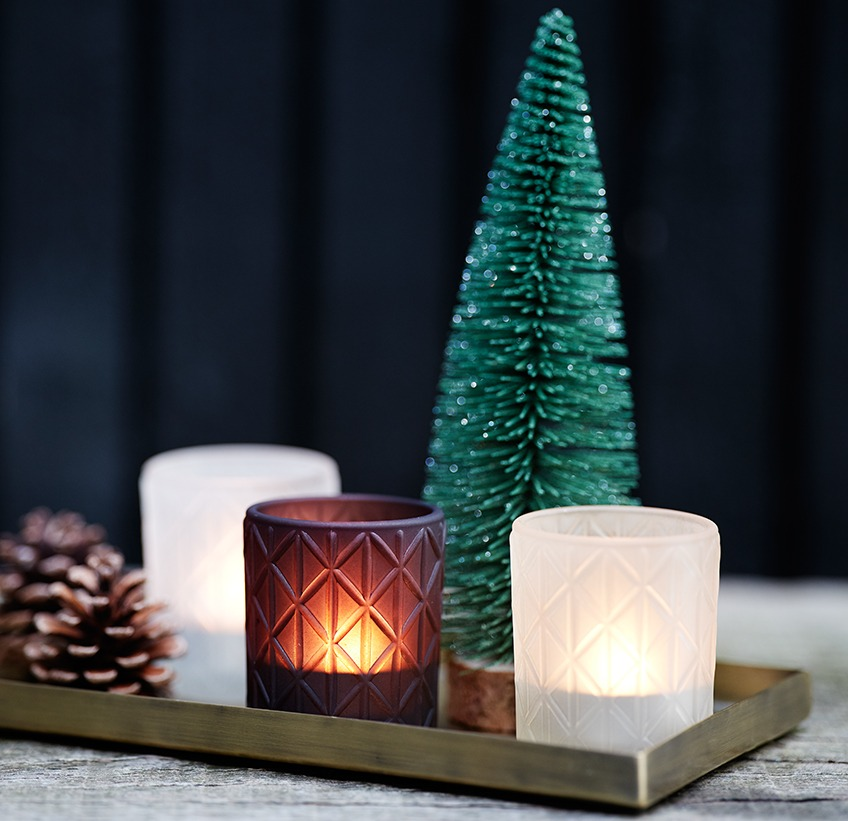 Tea light holders in glass on a metal tray with small Christmas tree and pinecones