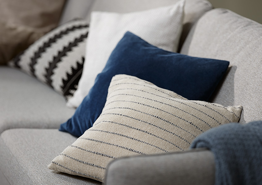 Multiple sofa cushions and cushion covers in different colours and materials