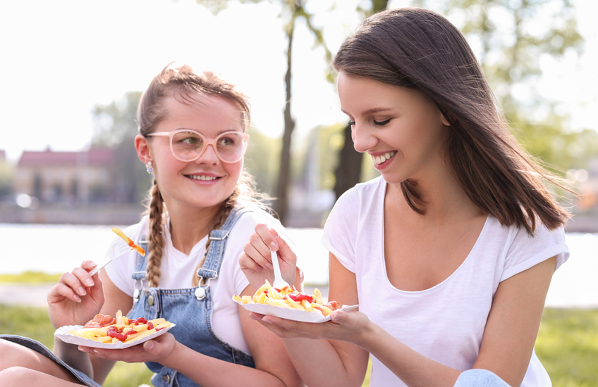 Two girls eating in a park in sunny weather